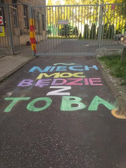 """zdjęcie bramy wejściowej do Liceum Czackiego a na asfaltowej drodze przed bramą duży kolorowy napis """"Niech moc będzie z Tobą"""""""